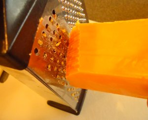 First off grate real cheddar cheese by hand. The better the cheese, the better the pimento cheese although a good brand of real cheddar cheese will suffice. I'm not that snobby!
