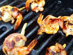 shrimp wrapped in bacon and skewered with sugar cane