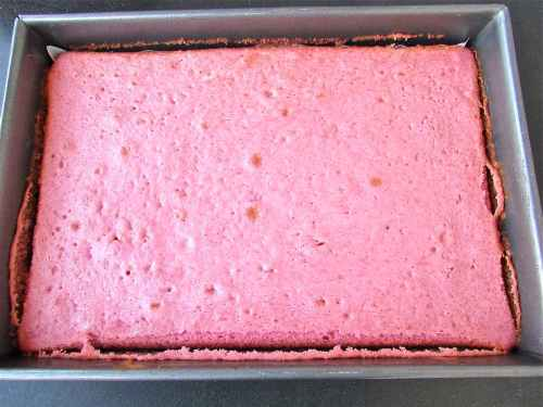 After baking, it is still pink! Allow to cool in the pan a bit, then remove to a rack and remove parchment paper. It should be completely cool before frosting!