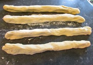 Punch the dough down, separate into 4 evenly sized balls and then roll out into 4 evenly sized strands.