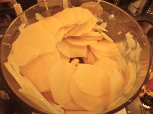 Sliced potatoes in the Cuisinart. You can also use a mandoline slicer to get uniform slices.